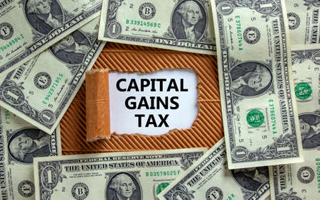 Capital gains tax symbol. The text 'Capital gains tax' appearing behind torn brown paper. Dollar bills. Business and capital gains tax concept.