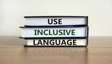 Use inclusive language symbol. Books with words 'Use inclusive language' on beautiful wooden table, white background. Business and use inclusive language concept. Copy space.