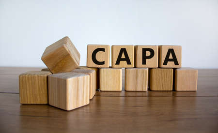 CAPA symbol. Concept word 'CAPA, corrective and preventive actions' on wooden cubes on a beautiful wooden table, white background. Business and CAPA concept. Copy space.