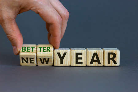 New better year concept. Businessman hand turns cubes and changes words 'new year' to 'better year'. Beautiful gray background. Business and new better year concept. Copy space.