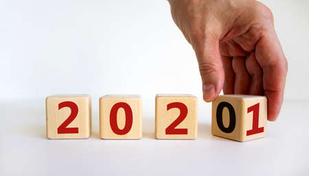 2021 new year symbol. Hand turns cubes and changes the year '2020' to '2021'. Beautiful gray background. Business and 2021 new year concept. Copy space.