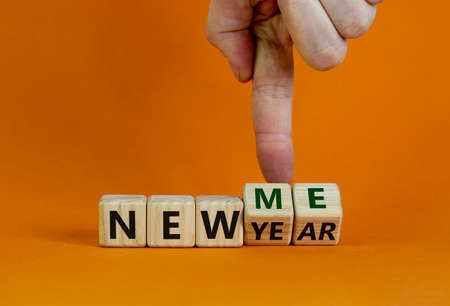 New year time. Male hand turns cubes and changes the words 'new year' to 'new me'. Beautiful orange background. Copy space. Business and new year - new me concept.