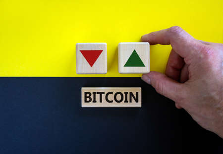 Bitcoin rate symbol. Businessman holds a cubes with up arrow. Wooden block with word 'bitcoin'. Beautiful yellow and black background. Copy space. Business and bitcoin rate concept.