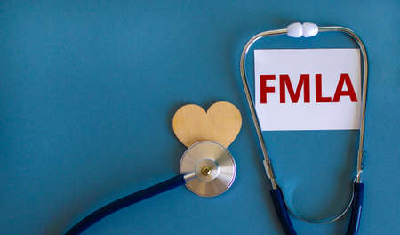 FMLA symbol. White card with word 'FMLA - family medical leave act' and stethoscope on blue background. Wooden heart. Medical and FMLA - family medical leave act concept, copy space.