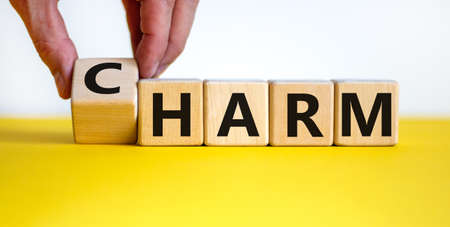 From harm to charm. Male hand turns the cube and changes word 'harm' to 'charm'. Beautiful yellow table, white background. Business and harm or charm concept. Copy space.
