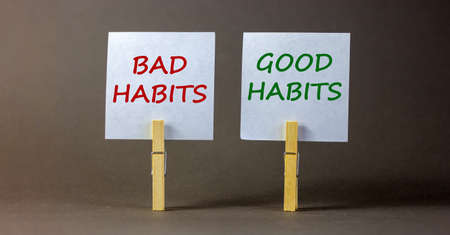 Bad or good habits symbol. Wooden clothespins with white sheets of paper. Words 'bad habits, good habits'. Beautiful gray background. Business and bad or good habits concept, copy space.