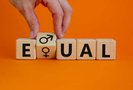 Gender eduality symbol. Male hand turns wooden cube with male and female symbol. Equal word. Business and gender equality concept. Beautiful orange background, copy space.
