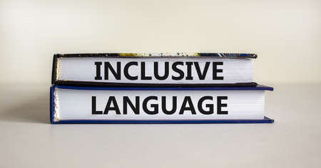 Inclusive language symbol. Books with words 'Inclusive language' on beautiful white background. Business and inclusive language concept. Copy space.