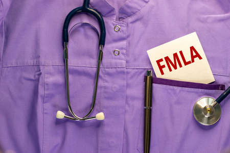 FMLA symbol. Medical uniform, white card with words 'FMLA - family medical leave act', metalic pen and stethoscope. Medical and FMLA - family medical leave act concept. Copy space.