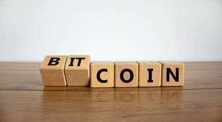 Bitcoin symbol. Turned wooden cubes and changed the word 'coin' to 'bitcoin'. Beautiful wooden table, white background, copy space. Business and bitcoin concept.
