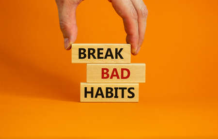 Break bad habits symbol. Wooden blocks with words 'break bad habits'. Male hand. Beautiful orange background, copy space. Business, psychological and break bad habits concept.