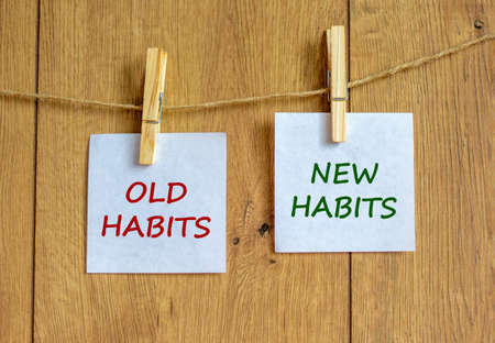 Old or new habits symbol. Wooden clothespins with white sheets of paper. Words 'old habits, new habits'. Beautiful wooden background. Business and old or new habits concept, copy space.