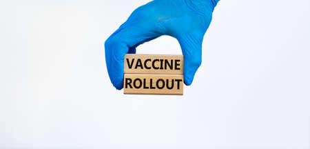 Vaccine rollout symbol. Hand in blue glove holds wooden blocks with words 'vaccine rollout'. Beautiful white background. Copy space. Medical and COVID-19 Pandemic Coronavirus concept.