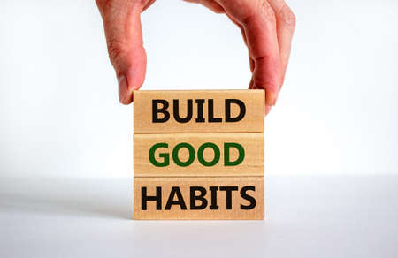 Build good habits symbol. Wooden blocks with words 'build good habits'. Male hand. Beautiful white background, copy space. Business, psychological and build good habits concept.