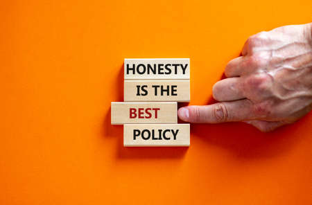 Honesty is the best policy symbol. Wooden blocks. Text 'honesty is the best policy', businessman hand. Beautiful orange background, copy space. Business and honesty is the best policy concept.