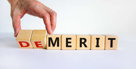Demerit or merit symbol. Male hand flips wooden cubes and changes words 'demerit' to 'merit'. Beautiful white background, copy space. Business and demerit or merit concept.