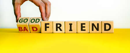 Good or bad friend symbol. Male hand turns wooden cubes and changes words 'Bad friend' to 'Good friend'. Beautiful white background. Business and friendship concept, copy space. 写真素材