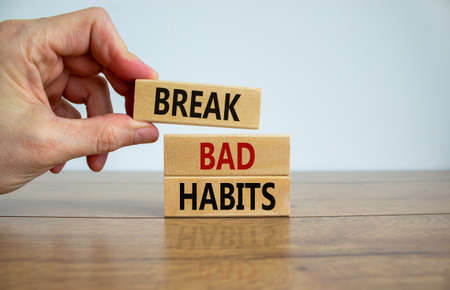 Break bad habits symbol. Wooden blocks with words 'break bad habits'. Male hand. Beautiful wooden table, white background, copy space. Business, psychological and break bad habits concept.