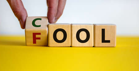 Do not be a fool just play cool symbol. Male hand turns wooden cubes and changes the word 'fool' to 'cool' on yellow table, white background, copy space. Business and fool or cool concept.