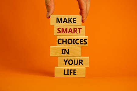 Make smart choice symbol. Concept words 'Make smart choice in your life' on wooden blocks on a beautiful orange background. Businessman hand. Business and make smart choice concept. Copy space.