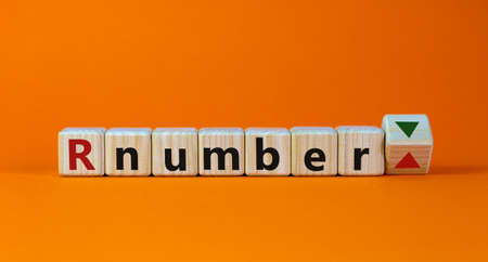 R - reproduction number up or down symbol. Wooden cubes with word R - reproduction number on beautiful orange background. Covid-19 pandemic R - reproduction number concept. 写真素材