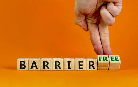 Barrier free symbol. Male hand turns wooden cubes and changes words 'barrier' to 'barrier free'. Business, inclusivity and barrier free concept. Beautiful orange background, copy space.