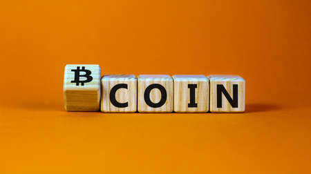 Bitcoin symbol. Turned the wooden cube and changed the word 'coin' to 'bitcoin'. Beautiful orange background, copy space. Business and bitcoin concept.