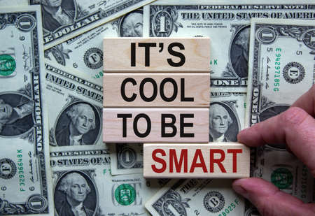 Be smart symbol. Wooden blocks form the words 'it is cool to be smart' on beautiful background from dollar bills. Male hand. Business and 'it is cool to be smart' concept. Copy space. Banco de Imagens