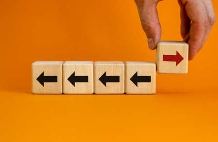 Hand holding wooden block with red arrow facing the opposite direction black arrows. Unique, think different, individual and standing out from the crowd concept Banco de Imagens