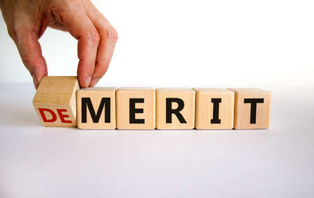 Demerit or merit symbol. Male hand flips the wooden cube and changes words 'demerit' to 'merit'. Beautiful white background, copy space. Business and demerit or merit concept. Banco de Imagens