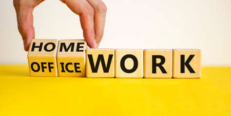 Back to normal. Hand turns cubes and changes words 'home work' to 'office work'. Beautiful yellow table, white background. Copy space, Business and home or office work concept. 写真素材