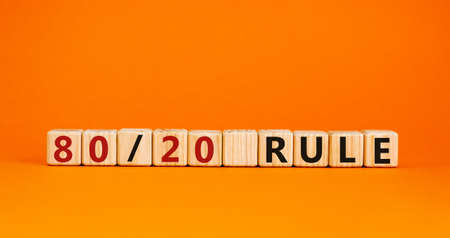 80 on 20 rule symbol. Wooden cubes with words '80 on 20 rule '. Beautiful orange background, copy space. Business and 80 on 20 rule concept.