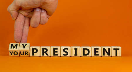 My or your president. Male hand turns cubes and changes words 'your president' to 'my president'. Beautiful orange background. Copy space. Political and my president concept.