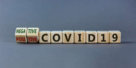 Turned cubes and changed words 'positive COVID19' to 'negative COVID19'. Beautiful gray background. Medical end covid19 test result concept. Copy space.