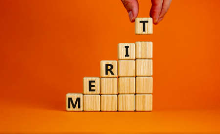 Merit symbol. Wood cubes with word 'merit' stacking as step stair on beautiful orange background, copy space. Male hand. Business and merit concept.