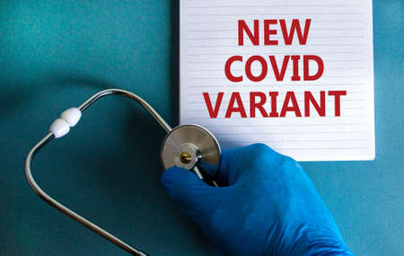 New covid variant symbol. Hand in blue glove with white card. Concept words 'New covid variant'. Stethoscope. Medical and COVID-19 pandemic new covid variant concept. Copy space. 写真素材
