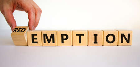 Redemption or emption symbol. Male hand turns a wooden cube and changes the word 'emption' to 'redemption'. Beautiful white background, copy space. Business and redemption concept. Banco de Imagens