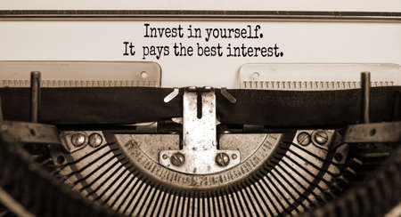 Invest in yourself symbol. Text 'invest in yourself it pays the best interest' typed on retro typewriter. Business and invest in yourself concept. Beautiful background. Sepia. Banco de Imagens