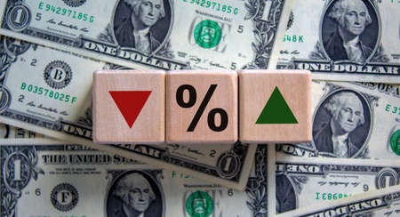 Change of Interest rates symbol. Wooden cubes with opposite the direction of an arrow symbolizing that the interest rates are going up or down. Business concept. Beautiful background from dollar bills. Stock fotó