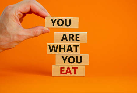 You are what you eat symbol. Stack of wooden blocks. Words 'You are what you eat'. Male hand. Beautiful orange background. Healthy eating concept. Copy space.
