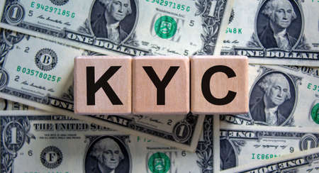 KYC - know your customer symbol. Concept word 'KYC - know your customer' on cubes on a beautiful background from dollar bills. Business and KYC - know your customer concept.