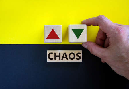 Time to chaos. Businessman holds a cubes with up icon. Wooden cubes with word 'chaos'. Beautiful yellow and black background. Copy space. Business and chaos concept.