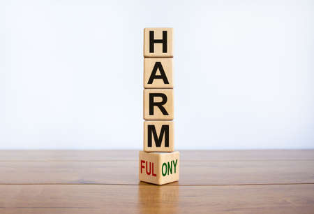 From harmful to harmony. Turned the wooden cube and changed the word 'harmful' to 'harmony'. Beautiful wooden table, white background. Business and harmful or harmony concept. Copy space.