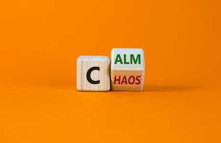 Stop chaos, time to calm. Turned a wooden cube and changed the word 'chaos' to 'calm'. Beautiful orange background, copy space. Business and chaos or calm concept. Stock Photo