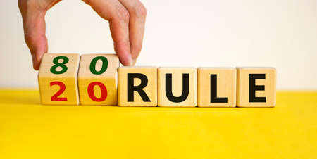 80 on 20 rule symbol. Pareto principle. Male hand flips wooden cubes with words '80 on 20 rule '. Beautiful yellow table, white background, copy space. Business and 80 on 20 rule, pareto concept.
