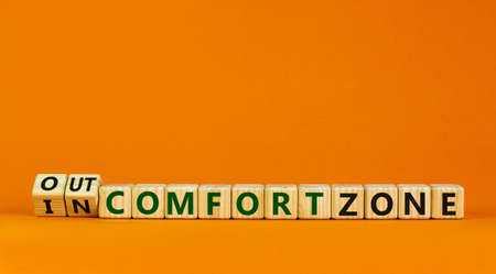 Out or in comfort zone symbol. Turned wooden cubes and changed words 'in comfort zone' to 'out comfort zone'. Beautiful orange background, copy space. Business, psychology concept. Banque d'images