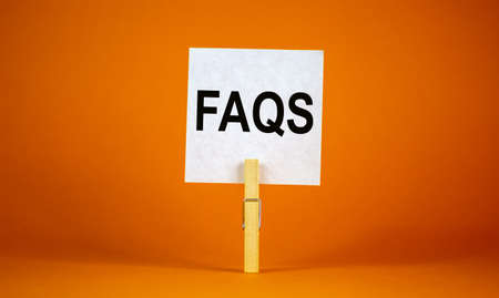 FAQS, frequently asked questions symbol. White paper on wooden clothespin. Words 'FAQS, frequently asked questions'. Beautiful orange background. Business and FAQS concept, copy space.