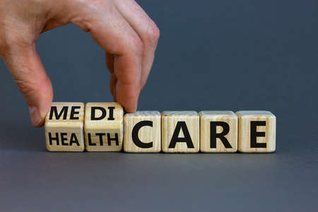 Medicare or healthcare symbol. Doctor turns cubes, changes the word 'healthcare' to 'medicare'. Beautiful gray background. Copy space. Medical, medicare or healthcare concept.