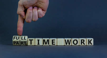Full or part time work symbol. Businessman turns cubes and changes words 'full-time work' to 'part-time work'. Beautiful gray background. Business and full-time work concept. Copy space.