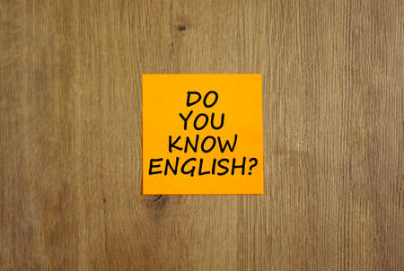 Do you know english symbol. Yellow sheet of paper. Words 'Do you know english'. Beautiful wooden background. Business, education and do you know english concept, copy space.